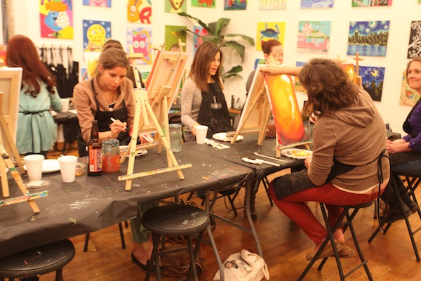 This class at Wine and Design includes a participant looking at the progression of her work of art, in awe (Staff photo by Morgan Johnson).