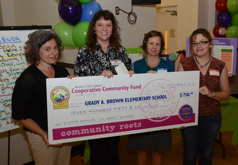 Weaver Street Market awarded a $750 grant from the Cooperative Community Fund to Grady Brown Elementary School during the Sept. 9 annual meeting. Making the presentation is CCF committee member Alicia Altmueller, left; and accepting for Grady Brown School are, left to right, Rachel Monschein, vice president, Grady Brown PTA; Jennifer Carson, grant writer for the Grady Brown Elementary School PTA; and  Rachel Kulberg, parent providing support for auquaponics projects. (Staff photo by Jock Lauterer