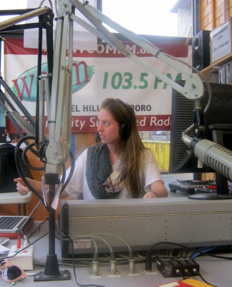 Simone Duval, a UNC-CH senior and member of Radio Latijam's production team, works the radio switchboard and signals to her fellow producers that they are live on air.