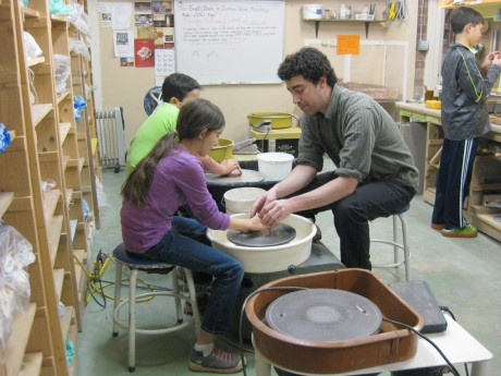 Ceramics teacher Jason Abide offers one-on-one help to Klara making a bowl at the pottery wheel during class.