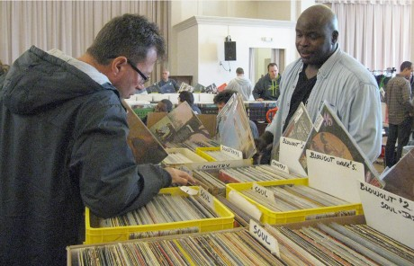 Craig Williams, a vendor from Richmond, Va., informs customers about his record collection as they sort through his albums. Craig Williams is one of 35 vendors at the Carrboro CD & Record Show. (Staff photo by Chloe Opper)