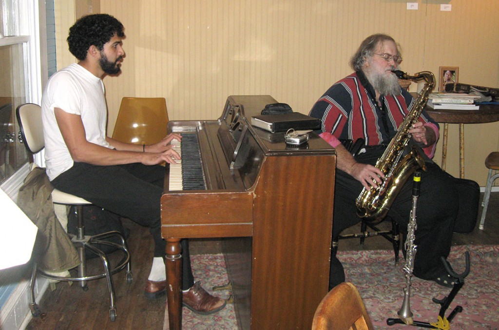 "Anuraag Pendyal, one of the members of Y'all Pendyal, plays the piano during one of his songs, ""Vitamin Water."" The other member of the band, Jim Lande, accompanies on the saxophone. (Staff photo by Chloe Opper)"