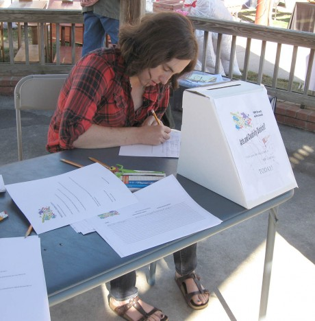 "Maria Soharz completes a Creative Carrboro survey at the Carrboro Farmer's Market. The survey asks takers what attracts them to Carrboro, how they define an arts district, and what they'd like to see in Carrboro. Survey responses include renting space for artists to use, creating interest groups based on art topics, and employing a high-speed municipal internet network. Soharz says she was happy to complete the survey because ""the people that speak are the people that are heard."""