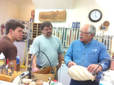 Frank Penta, a founding member of the Chapel Hill Woodturners, discusses woodturning with Cedar Ridge student Hunter Thompson, left, and CHHS furniture and cabinetmaking instructor Keith Yow. (Photo courtesy of CH Woodturners)