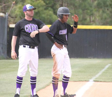 Carrboro baseball coach Shaughn Neal (left) discusses strategy with Carrboro senior Ben West (right) at third base during the Jaguars' game against Northwood. Carrboro never trailed in their 4-2 victory over Northwood in Pittsboro, North Carolina.