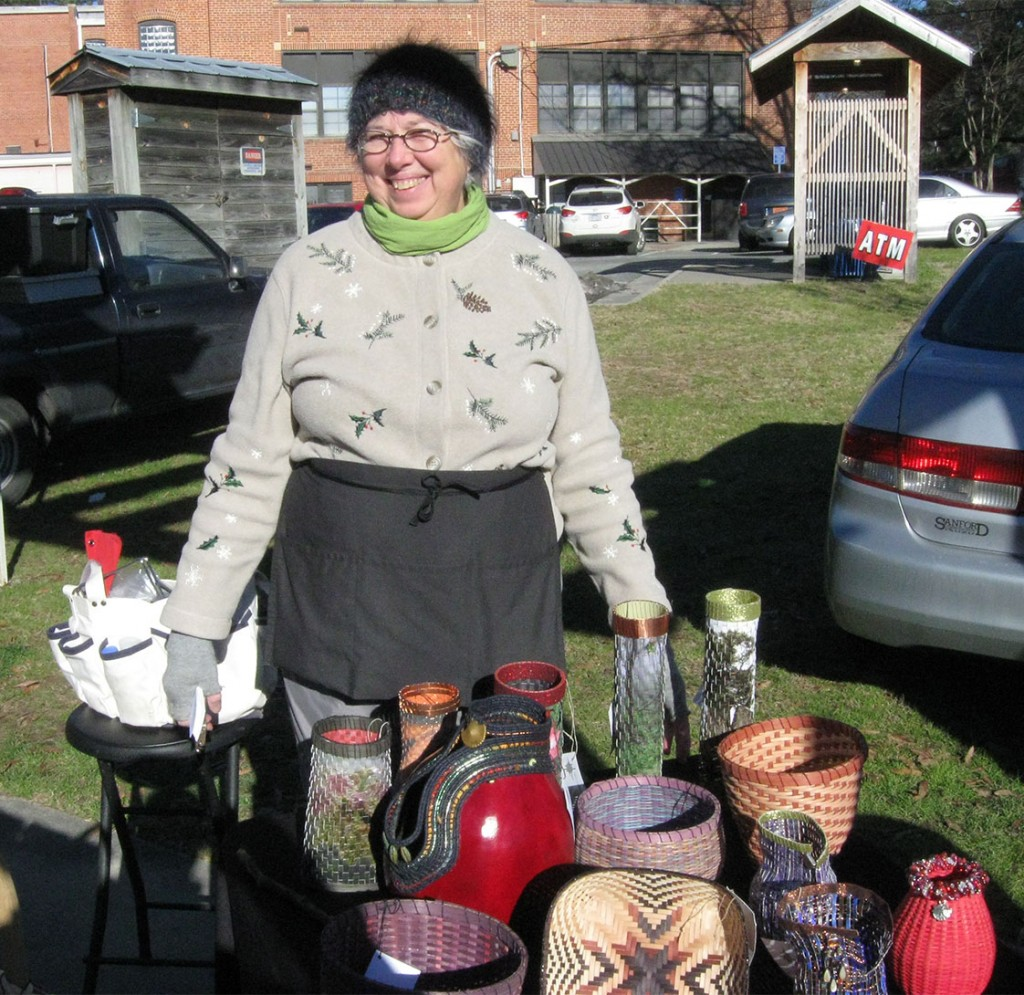 Susan Laswell poses in front of her baskets at the Carrboro Farmers' Market on Jan. 31. Laswell has been weaving regularly since 1977 and has sold her art pieces at the Carrboro Farmers' market for almost 14 years. (Staff photo by Ben Coley)