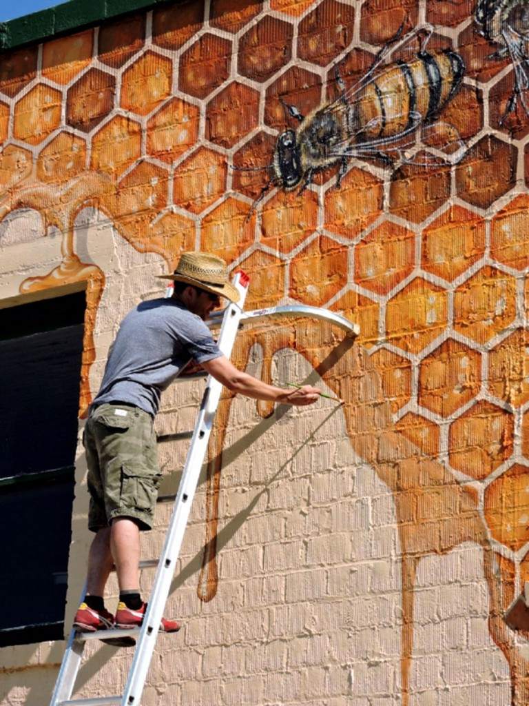 The Good of the Hive project started here, in LaBelle, Florida, where Willey can be seen painting the first of what he hopes will be about forty murals. (Photo courtesy of Matthew Willey)