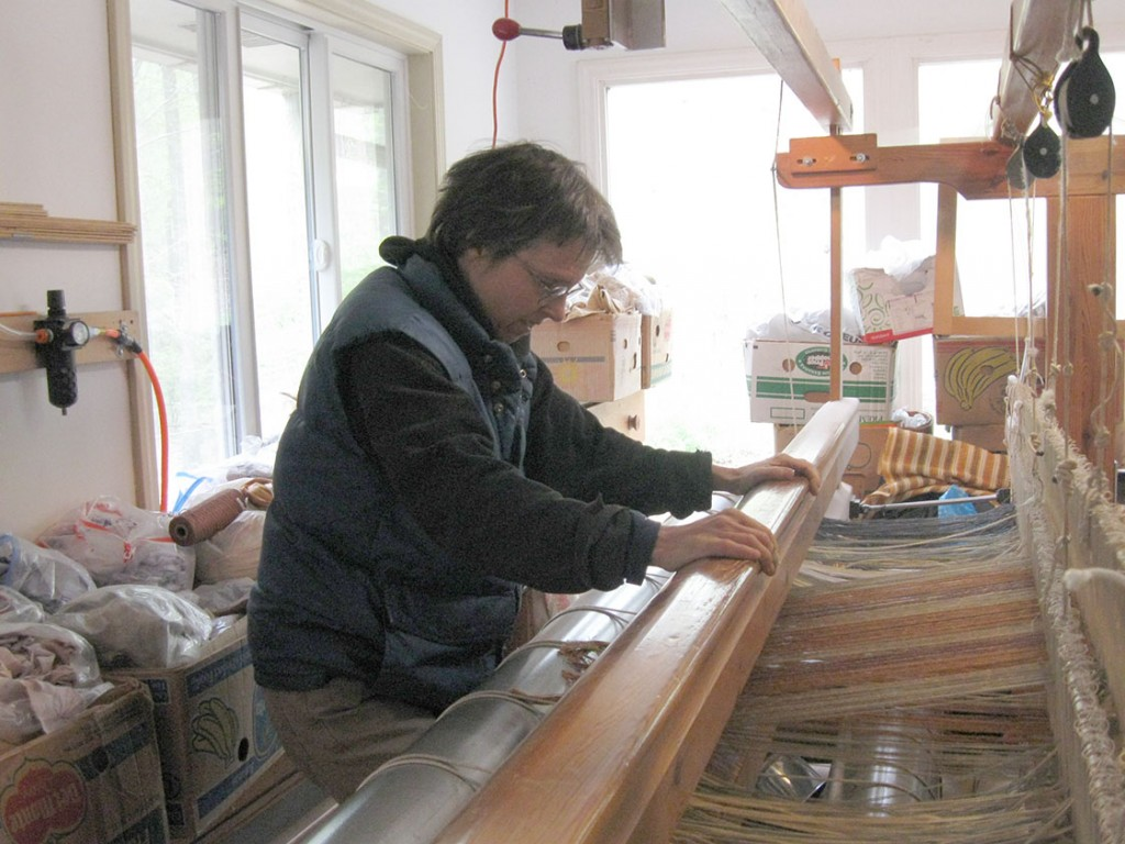 Carol Blackmore uses the Swedish Glimakra Sovereign loom in her makeshift workshop, where she is surrounded by boxes of fabric. Blackmore said that she sometimes teaches weaving, and that she can usually teach someone in about five sessions (Staff photo by Ben Coley).