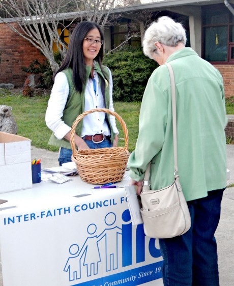 "Vicky Kim, resident of Carrboro and IFC volunteer, hands out buttons and informs residents before the Carrboro Board of Alderman public hearing on Tuesday, March 22. Kim said she understands the concerns citizens have, but is also a strong supporter of the IFC. ""This text change merely documents that as a town we allow social organizations, not just restaurants and bars, to provide hot meals in Carrboro. And that it's permissible for anyone who's hungry, whether they have money or not, to eat in Carrboro. I think we have an exciting opportunity with the progressive FoodFirst program to better serve the 21,000 people who live in poverty and are food insecure, right here in Orange County."" (Staff photo by Janell Smith)"